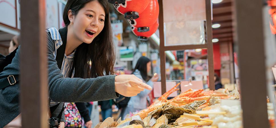 市場で魚を買う女性